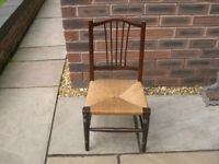 A wood framed child's chair with attractive rush seat.