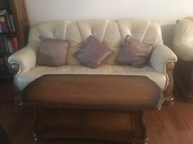 CREAM LEATHER SOFA SETWOODEN FRAMED ONE 3 SEATER AND TWO SINGLE ARM CHAIRS, A FOOTSTOOL AND 3 TABLES