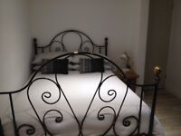 Wrought iron double bed with wooden slatted base. Excellent condition.