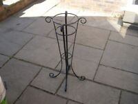 An attractive black metal planter stand.