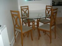 Glass circular dining table & four chairs in wrought iron design