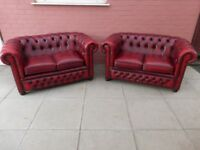 A Pair Of Oxblood Red Leather Chesterfield Two Seater Sofas