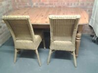Extending pine dining table with 4 wicker chairs