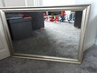 Large wall mirror with silver coloured frame.