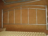 Silver coloured metal double bed frame with slats.