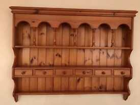 Wall mounted pine plate rack with integral drawers.