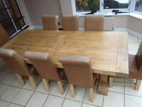 Large solid oak table with 8 leather chairs.