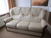 Three piece suite. Leather with wooden trim. Three seat sofa, two armchairs and footstool. Cream