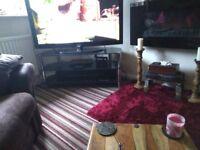 TV unit 54 inces wide. Black glass. Chrome legs. Excellent condition. Pick up only. Fifteen pounds.