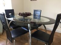 Glass top black dining table with four moedern looking chairs