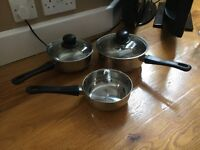 SET OF THREE PANS WITH BLACK HANDLES - TWO LIDS INCLUDED