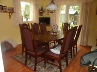 A Parker Knowles dinning table and eight chairs including two carvers