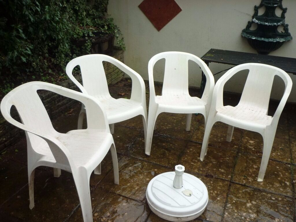 4 plastic patio chairs plus water filled umbrella base