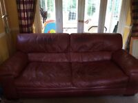 Two matching three seater dark red leather sofas