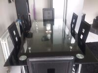 Two tier black glass table and 6 chairs