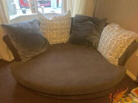 Corinne Cuddler Sofa with 4 grey and patterns cushions.