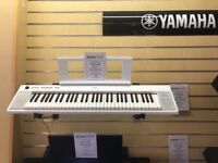 White Yamaha NP-12 electric keyboard with stand
