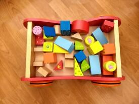 Colourful wooden building blocks, with wooden storage car