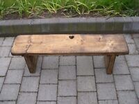 A wooden garden bench with heart shaped cut out.