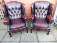 A pair of oxblood red leather chesterfield armchairs