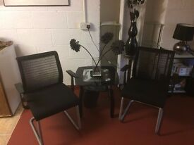 Pair of black mesh chairs with coffee table.