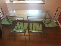Glass Dining table and 4 chairs. The dining table is in good condition collection only please.