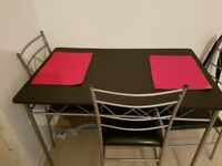 Black and silver dining table with 4 chairs