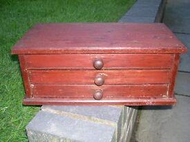 An old, small three drawer storage box.