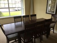 Solid wood dining table and matching chairs.