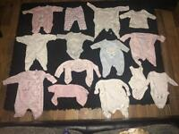New born baby girl and unused clothes.