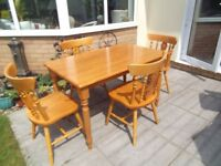 Pine Kitchen table and 4 farmhouse-style chairs.Used but good condition. Repair to one chair rail