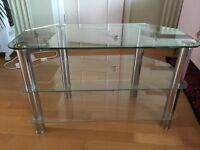 Glass television stand with three shelves and chrome legs