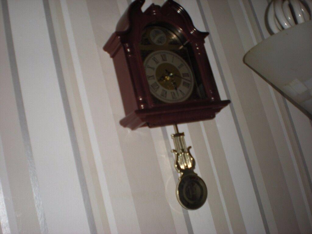Wall clock with pendulum swinging