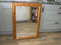 A medium size pine framed mirror with bevelled edges.