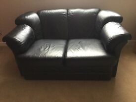 Black leather 2 seater and 3 seater sofas.