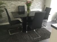Black high gloss dining table and chairs in good condition cost £500 new quick sale for £100