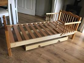Child's wooden bed with drawer on wheels.