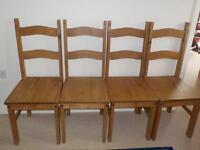 Four solid wood dining chairs