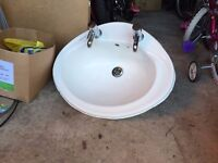 Bathroom sink for use in a vanity unit including taps