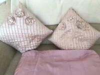 Pink silk cushions and pink throw over bed