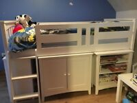 white cabin bed with ladder, pull out desk, underneath free standing furiture.