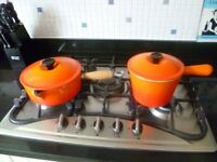 Two Le Creuset sauce pans, orange, with lids