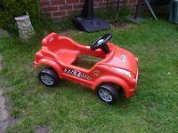 Toddler sit in pedal car.