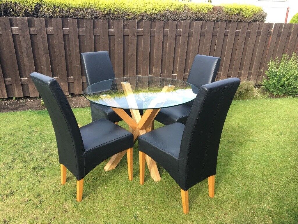 Round Wood Based Glass Dining Table And Four Black High