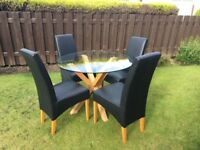 Round wood based glass dining table and four black high back chairs