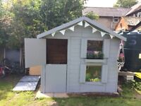 Playhouse with handmade steps to a sitting platform, den area underneath with stable door.
