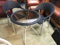 BLACK PLASTIC AND GLASS TABLE AND TWO CHAIRS