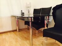 Dinning table , glass top and six chairs , chrome legs , leather effect chairs