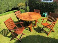 Solid teak garden table (119cm) and 4x folding arm chairs