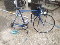 Two Vintage bicycles blue Raleigh racing bike one purple Peugeot racing bike.